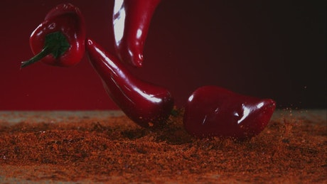 Chili peppers falling and bouncing into red powder