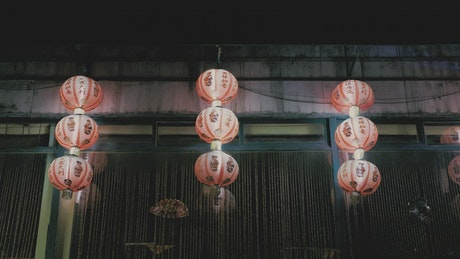 Chinese lamps on a wall at night