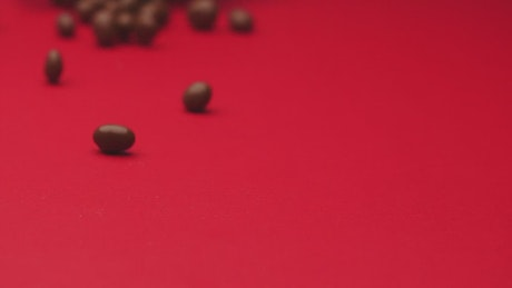 Chocolate beans rolling on a red surface