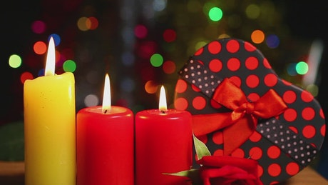 Christmas candles next to a heart shaped gift
