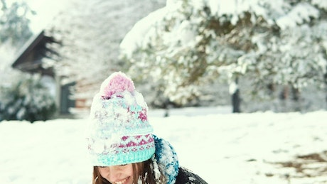 Cinematic of woman tossing up snow in winter landscape