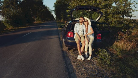 Cinematic view of couple sitting on car in countryside