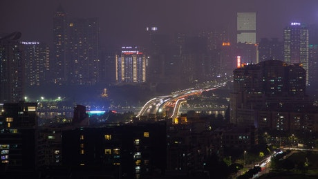City covered with buildings and cars at night