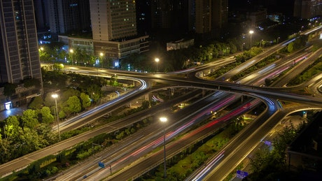 City cross roads with fast traffic at night