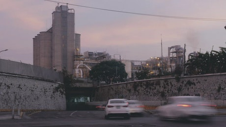 City traffic near a factory at sunset, time-lapse