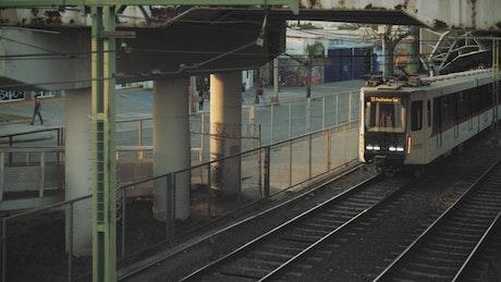 City train driving under a bridge
