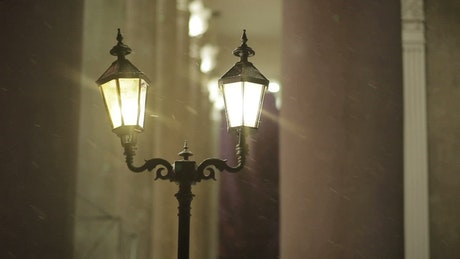 Classic street lights while it's snowing
