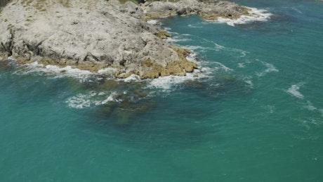 Clean coastal water breaking against rocks