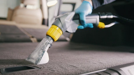 Cleaning a car carpet with a vacuum cleaner