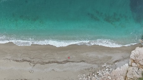 Clear sea and small waves breaking on the shore
