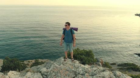 Climbed man on the rocky seashore