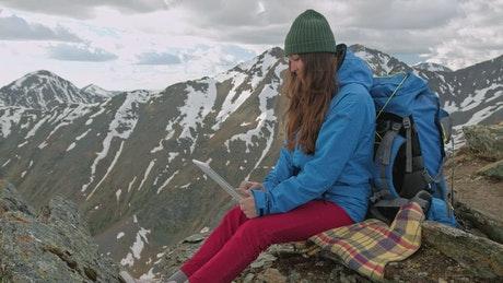 Climber using her tablet in the mountains