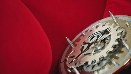 Clock with visible gears on red background