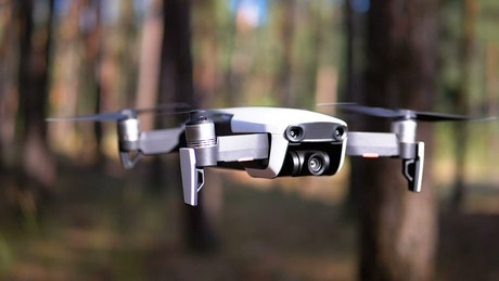 Close up of a drone hovering in the woods