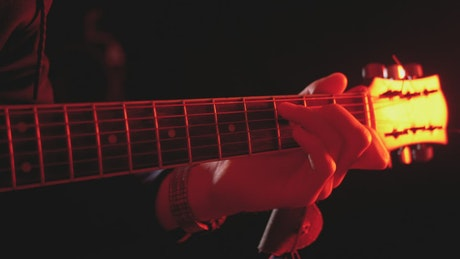 Close up of a hand playing the guitar