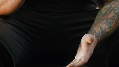Close up of a man with a tattoo clapping his hands