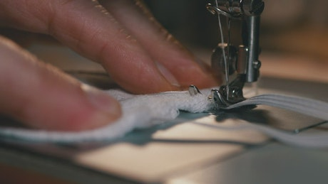 Close up of a person sewing a face mask