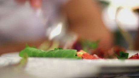 Close up shot of a person eating salad with a fork