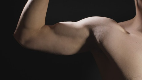 Close up to the bicep of a man on black background