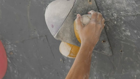 Close up tracking view of a man climbing a wall