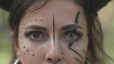 Closeup of devil makeup on dancer in forest