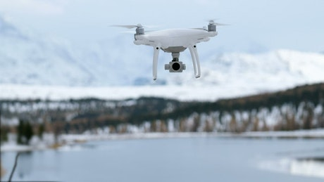 Closeup of drone hovering over winter lake