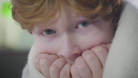 Closeup of fearful little boy wrapped in blanket