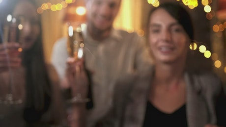 Closeup of friends toast with champagne and holiday lights