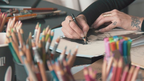 Closeup of graphic designer sketching on desk in studio