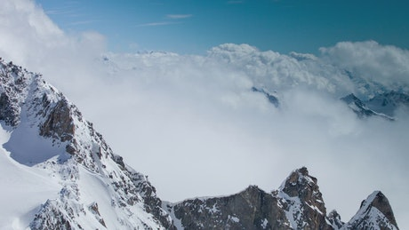 Clouds atop snow-capped mountains