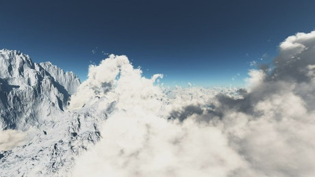 Clouds between snow capped mountains