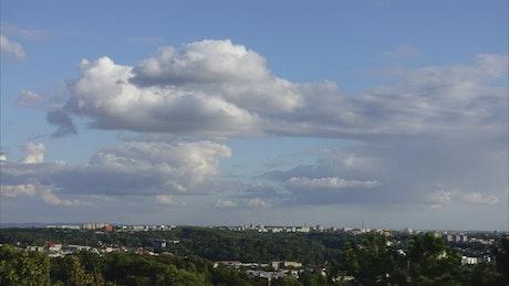 Clouds casting shadows over city woodland