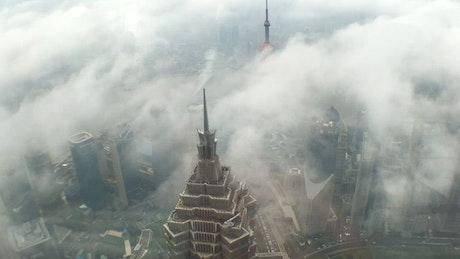 Clouds covering a skyscraper in Shanghai