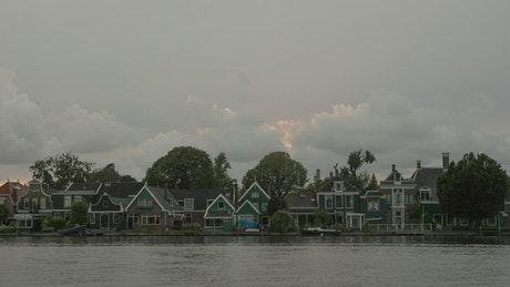 Clouds moving across river houses