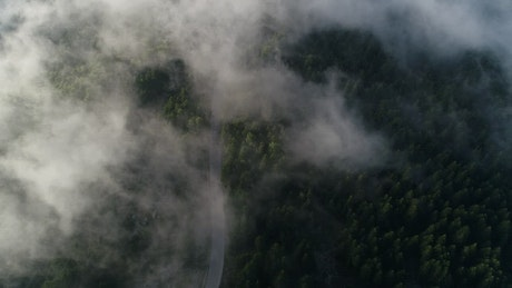 Clouds parting over a mountain road