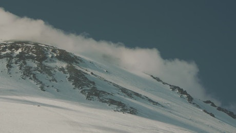Clouds rolling down a snowy mountain