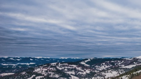 Cloudy sky over winter forested mountains