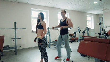 Coach supervising squats of fitness woman