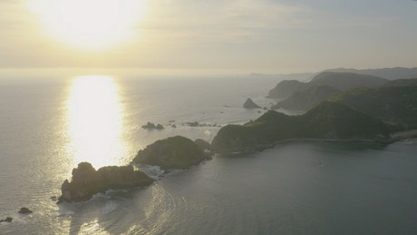 Coast with islands and mountains covered with vegetation during a sunset