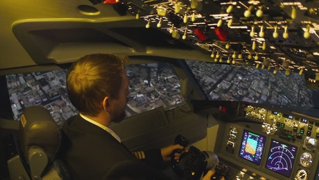 Cockpit view of the pilot flying above the city