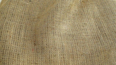 Coffee beans falling into a cloth sack