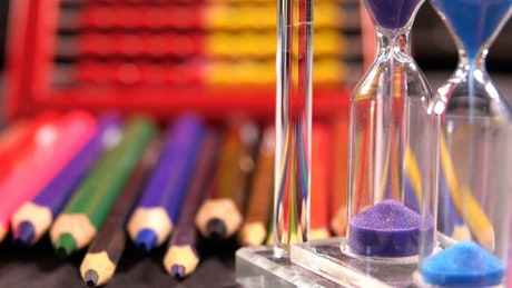 Colored hourglasses and school supplies