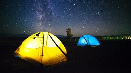 Colorful lit tents with time lapse of night sky and stars