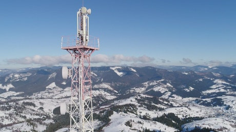 Communications tower in the snowy mountains, spinning aerial shot