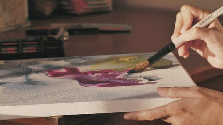Concentrated artist painting a picture with a brush