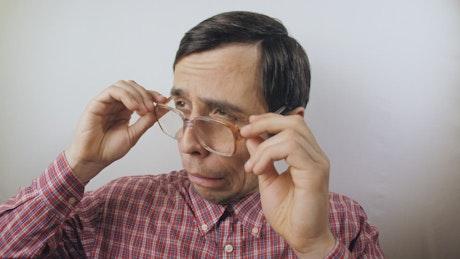 Confident nerdy man puts on his glasses