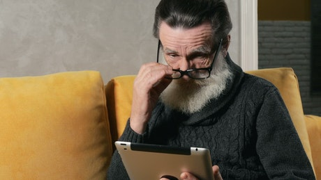 Confused elderly man using a tablet