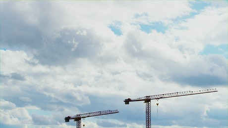 Construction crane towers under cloudy sky