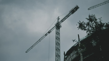 Construction crane with an airplane flying past