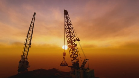 Construction cranes in front of the sunset